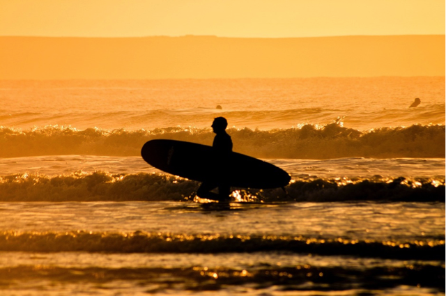 Man in surf at Woolacombe beach in sunset